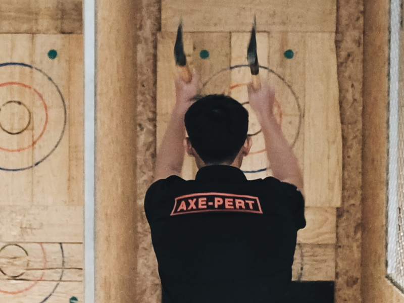 Picture of one guy throwing two axes at The Axe Factor