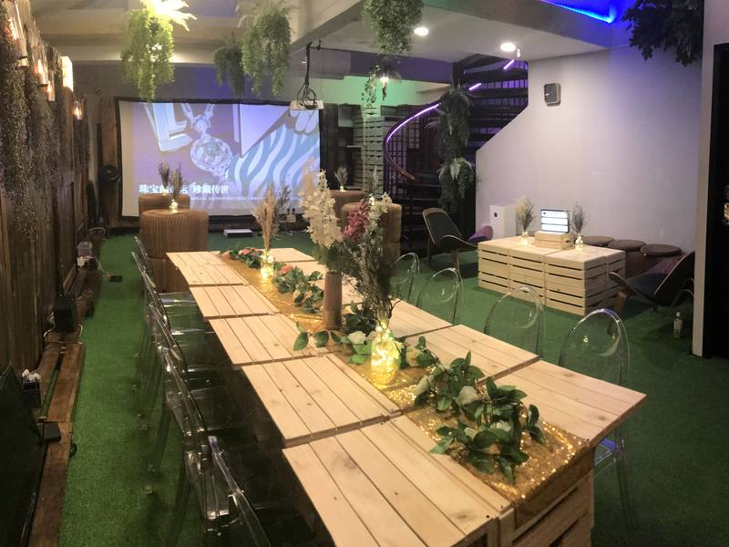 Wooden tables and transparent chairs with flowers at the event space Into the Woods