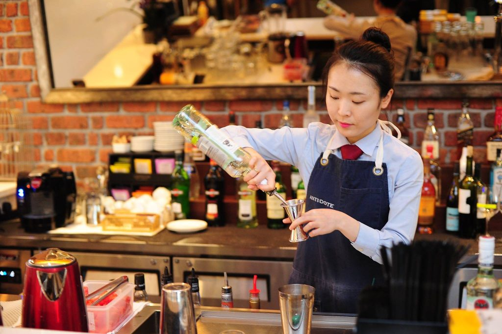 Bartender pouring drinks at the queen and mangosteen